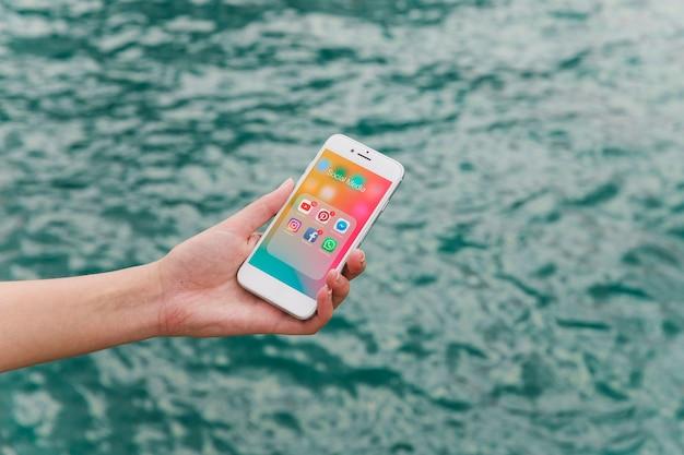 Weibliche hand, die mobiltelefon mit social media-benachrichtigungen auf schirm zeigt Kostenlose Fotos
