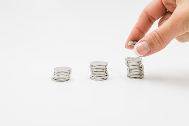 Weibliche hand, die münzen auf stapel setzt Kostenlose Fotos