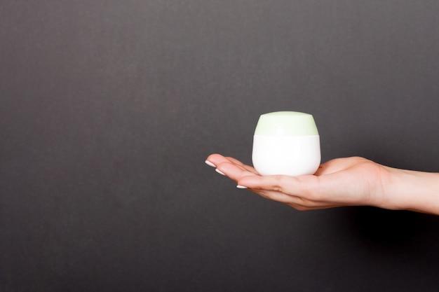 Weibliche hand, die sahneflasche lotion lokalisiert hält. mädchen geben kosmetische produkte des glases auf schwarzem hintergrund Premium Fotos