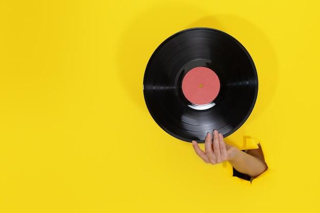 Weibliche hand, die schallplatte durch zerrissenes loch in der gelben papierwand hält. minimalistisches retro-konzept Premium Fotos