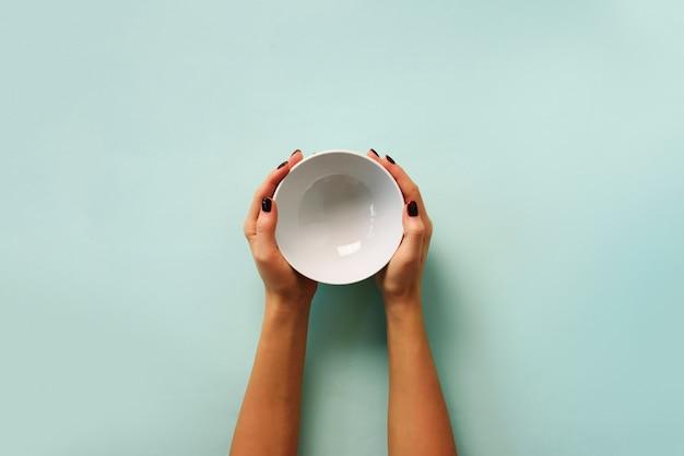 Weibliche hand, die weiße leere schüssel auf blauem hintergrund mit kopienraum hält. Premium Fotos