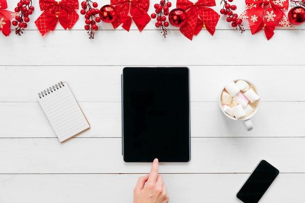 Weibliche hand. frau, die an einem bürotisch mit weihnachtsfestlichen dekorationen arbeitet Premium Fotos