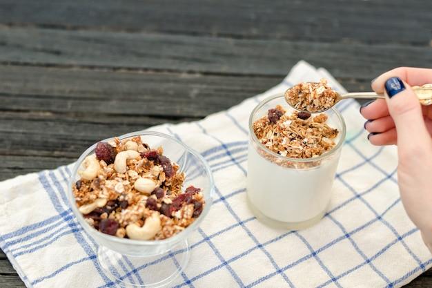 Weibliche hand gießt in joghurt müsli. traditionelles amerikanisches frühstück Premium Fotos