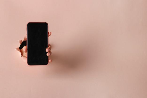 Weibliche hand hält smartphone durch rundes loch in rosa papier Premium Fotos