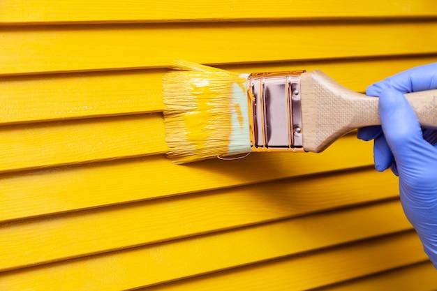 Weibliche hand im gummihandschuh mit bürstenmalereiholztür mit gelber farbe Premium Fotos