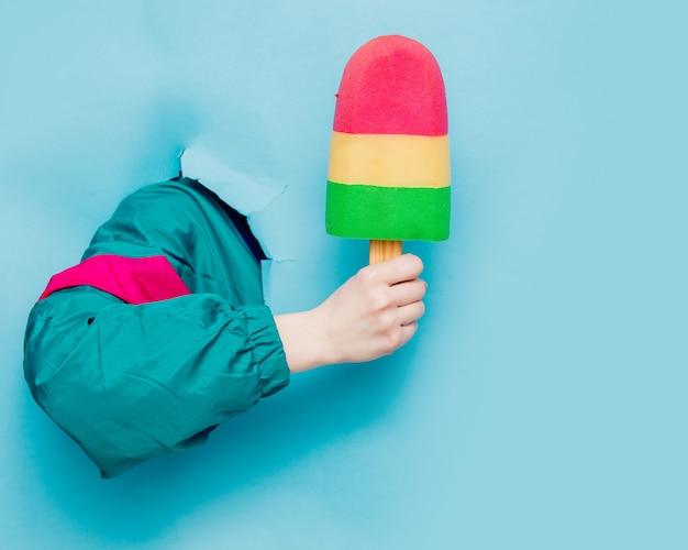 Weibliche hand in der jacke der art 90s, die eiscreme hält Premium Fotos