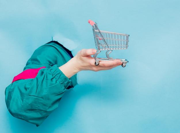 Weibliche hand in der jacke der art 90s, die supermarktwarenkorb hält Premium Fotos