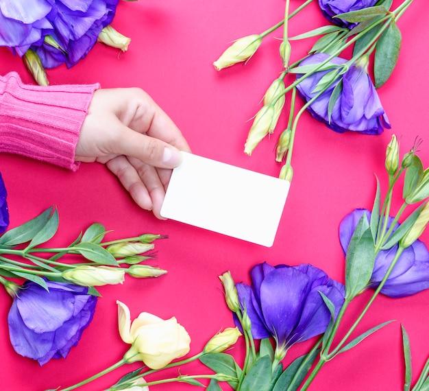 Weibliche hand in der rosa strickjacke, die eine leere weißbuchvisitenkarte hält Premium Fotos