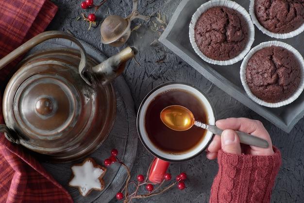 Weibliche hand mischt tasse tee mit einem löffel an einem kalten morgen im fall Premium Fotos