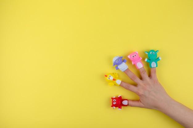 Weibliche hand mit 5 fingerpuppen: kuh, schaf, huhn, schwein. das konzept der kindlichen entwicklung. ort zum kopieren. flach liegen. Premium Fotos