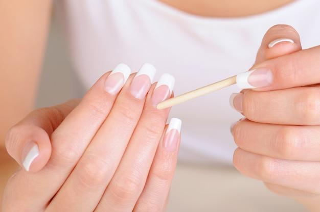 Weibliche hand mit einem kosmetikstift zum reinigen der nagelhaut Kostenlose Fotos