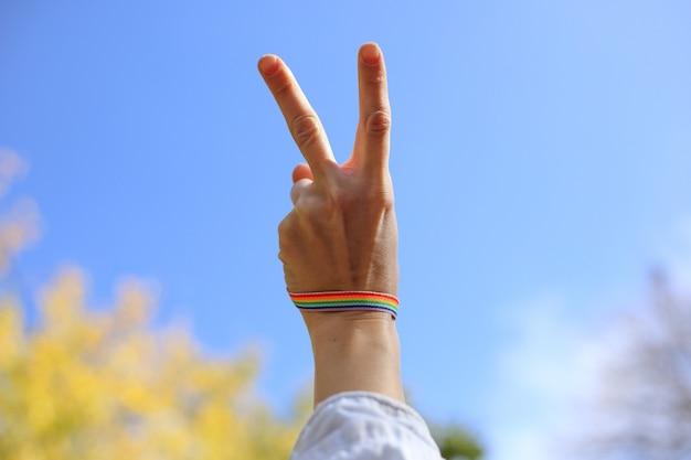 Weibliche hand mit regenbogenarmband zeigt siegeszeichen auf dem hintergrund des blauen himmels. lgbt-konzept Premium Fotos