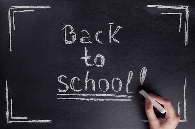 Weibliche hand schreibt die phrase zurück zu schule mit weißer kreide auf schwarze tafel. Premium Fotos