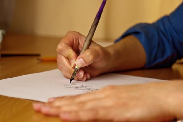 Weibliche hand schreibt mit dem tintenstift auf ein weißbuchblatt mit streifen. Premium Fotos