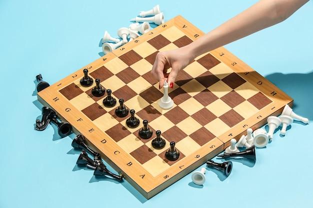 Weibliche hand und schachbrett, spielkonzept. Kostenlose Fotos