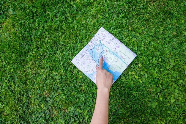 Weibliche hand zeigt einen finger auf einer topografischen karte auf dem gras Premium Fotos