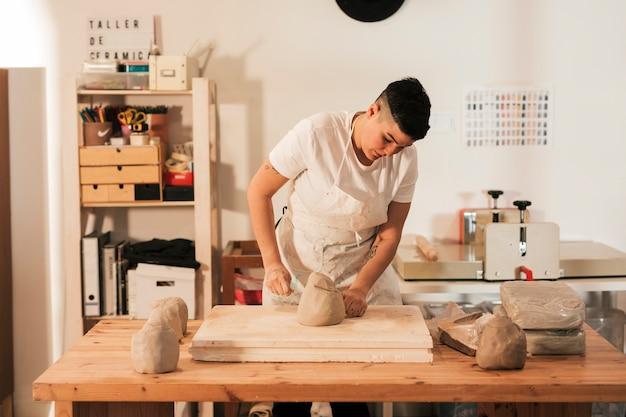 Weibliche handwerkerin, die auf dem tisch einen gekneteten lehm mit thread schneidet Kostenlose Fotos