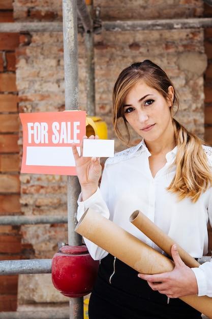 Weibliche immobilienmakler zeigt visitenkarte Kostenlose Fotos