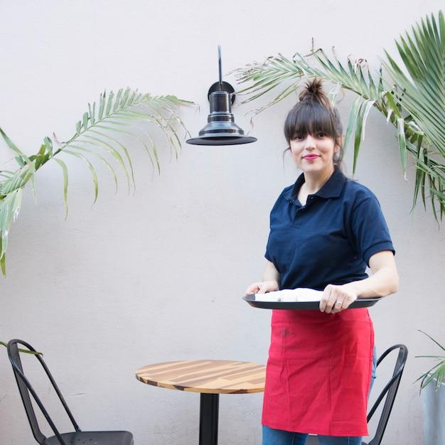 Weibliche kellnerin, die außerhalb des cafã © hält behälter steht Kostenlose Fotos