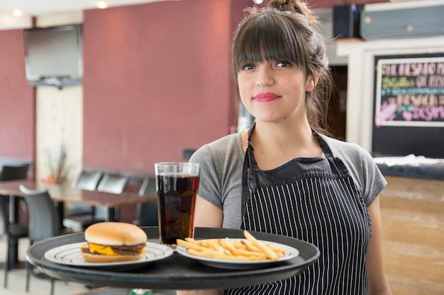Weibliche kellnerin, die behälter des cocktails hält; hähnchen burger und pommes frites Kostenlose Fotos