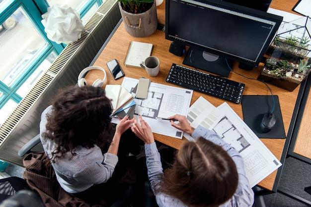 Weibliche konstrukteure diskutieren ein projekt und nehmen die endgültige korrektur der farbe im büro vor. draufsicht. Premium Fotos