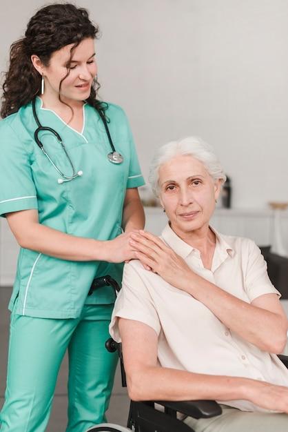Weibliche krankenschwester, die der älteren frau unterstützt, die auf rollstuhl sitzt Kostenlose Fotos