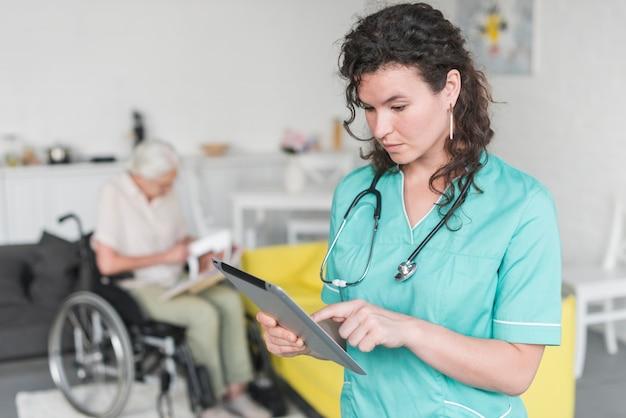 Weibliche krankenschwester, welche die digitale tablette steht vor der älteren frau sitzt auf rollstuhl verwendet Kostenlose Fotos