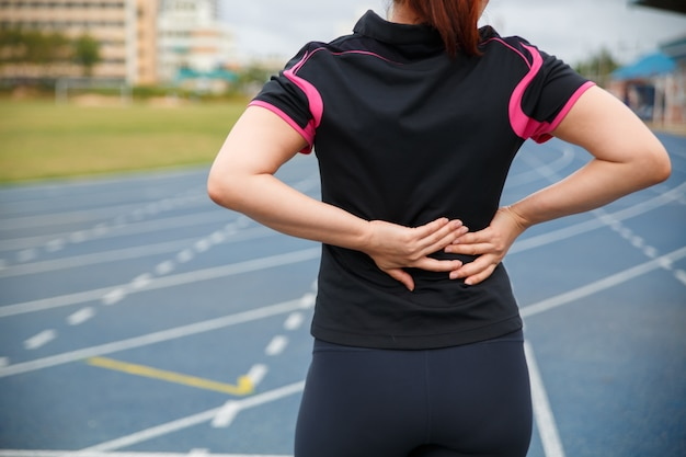 Weibliche läuferathletenrückenverletzung und -schmerz. frau, die unter schmerzlichem hexenschuss beim laufen auf der blauen gummierten laufbahn leidet. Premium Fotos