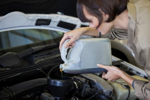 Weibliche mechaniker gießt öl schmiermittel in den automotor Kostenlose Fotos