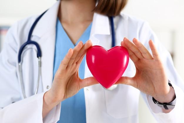 Weibliche medizinarzthände, die rotes herz halten Premium Fotos