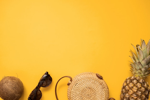 Weibliche mode-ausstattungsebenenlage des bunten sommers mit bambustasche und sonnenbrille Premium Fotos