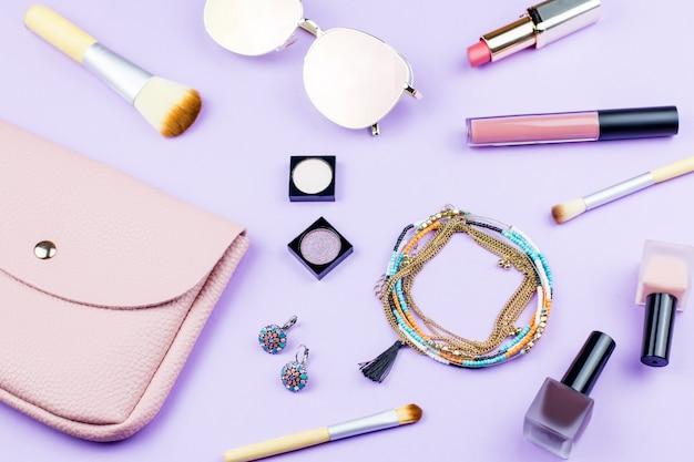 Weibliche modeaccessoires auf pastellhintergrund. rosa geldbörse, verspiegelte sonnenbrille, schmuck, make-up-artikel. Premium Fotos