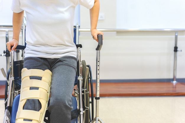 Weibliche patienten tragen knie-stützvorrichtungen, um die bewegung während des aufstehens vom rollstuhl zu reduzieren. Premium Fotos