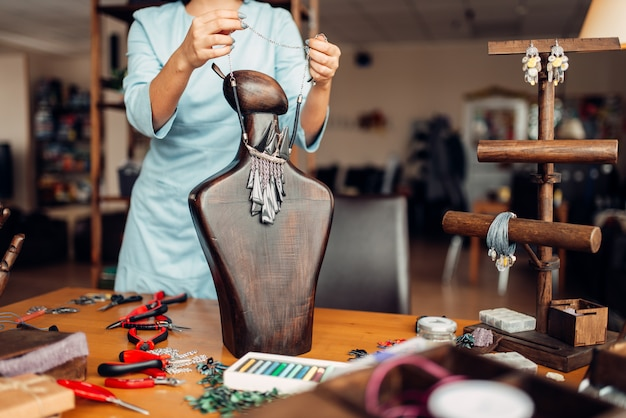 Weibliche person, die an handgemachter halskette auf einer hölzernen schaufensterpuppe, handarbeit versucht. weiblicher handwerker am arbeitsplatz im kunststudio Premium Fotos