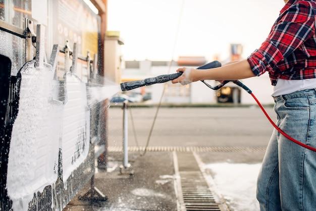 Weibliche person mit hochdruckwasserpistole in den händen reinigt automatten, berührungslose autowaschanlage. junge frau auf selbstbedienungsautowäsche. fahrzeugreinigung im freien am sommertag Premium Fotos