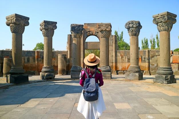 Weibliche reisende beim besuch der kathedrale von zvartnots, unesco-weltkulturerbe in der armenischen provinz armavir Premium Fotos