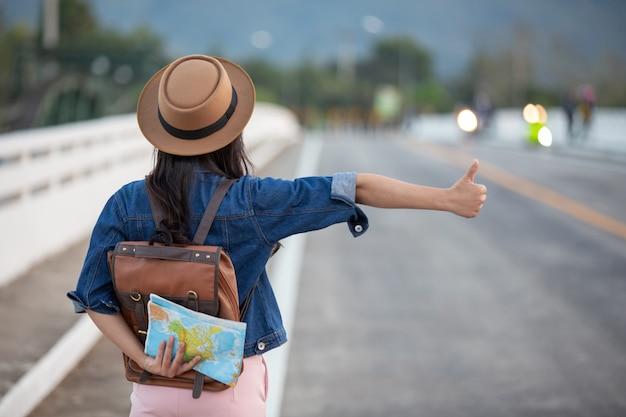 Weibliche reisende, die autos auf der straße wellenartig bewegen Kostenlose Fotos