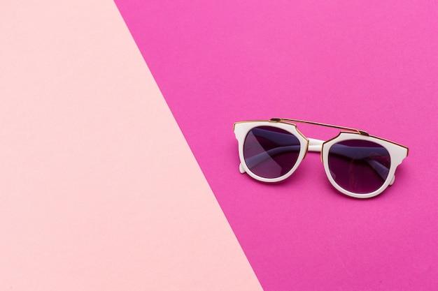 Weibliche sonnenbrille auf einem bunten vibrierenden hintergrund Premium Fotos