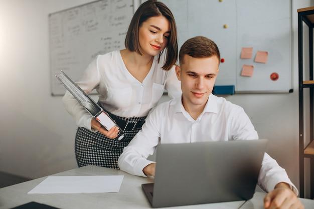 Weibliche und männliche kollegen, die im büro arbeiten Kostenlose Fotos