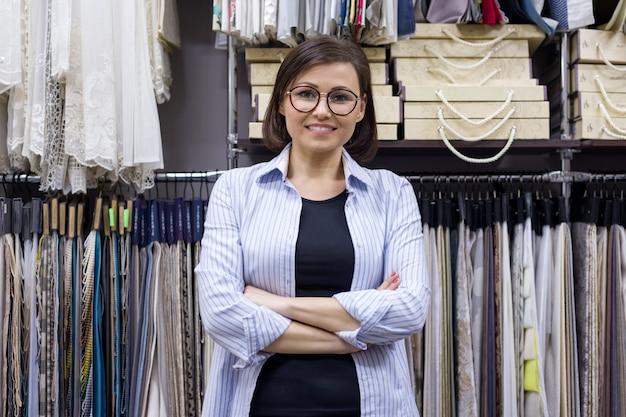 Weibliche verkäuferin, innenarchitekt im ausstellungsraum Premium Fotos