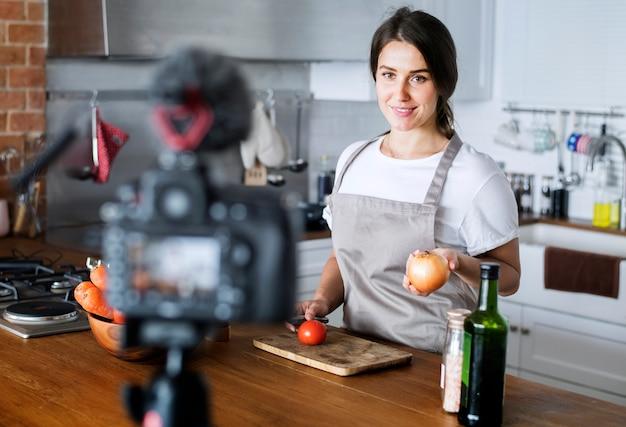 Weibliche vlogger-aufnahme, die zu hause in verbindung stehende sendung kocht Premium Fotos