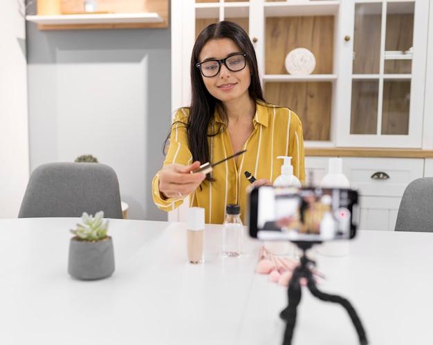 Weibliche vloggerin zu hause mit smartphone und empfohlenen produkten Kostenlose Fotos