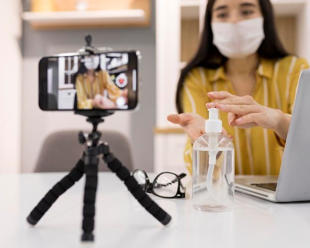 Weibliche vloggerin zu hause mit smartphone und händedesinfektionsmittel Kostenlose Fotos