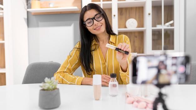 Weibliche vloggerin zu hause mit smartphone und make-up-produkten Kostenlose Fotos