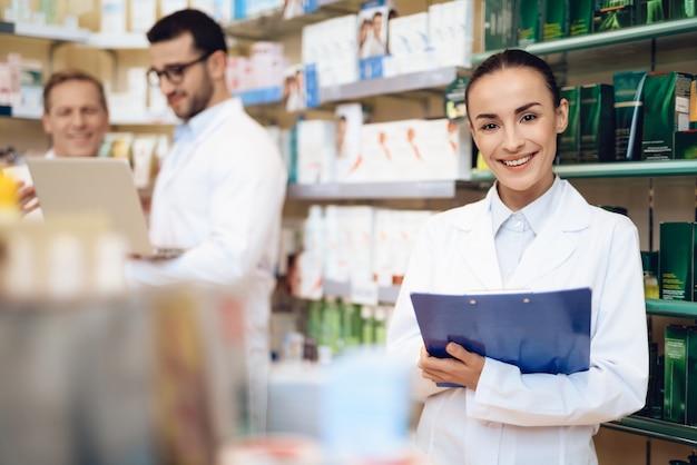 Weiblicher apotheker hält einen ordner mit papieren in einer apotheke. Premium Fotos