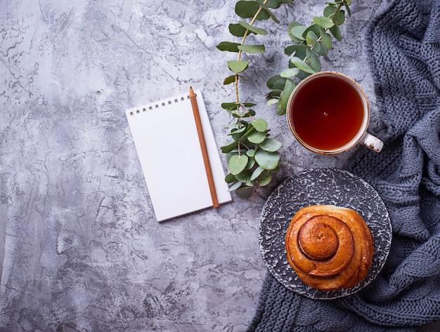 Weiblicher arbeitsplatz mit brötchen, tasse tee und notizbuch Premium Fotos