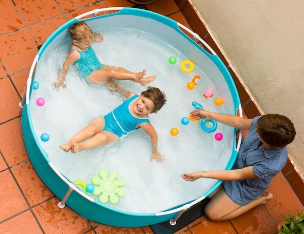 Weiblicher babysitter mit kleinen mädchen am pool Kostenlose Fotos