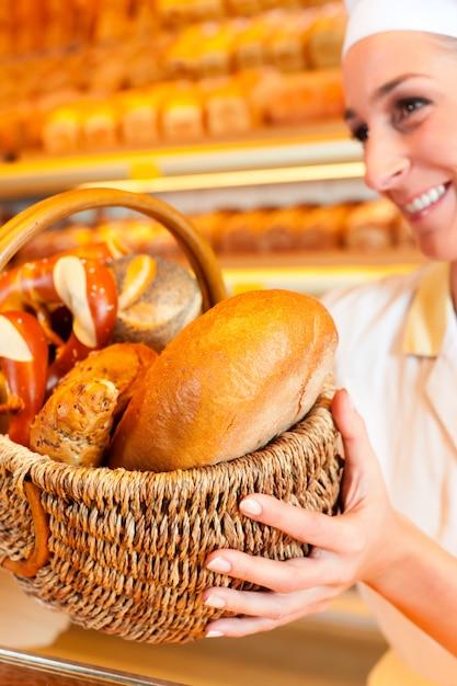 Weiblicher bäcker, der brot durch korb in der bäckerei verkauft Premium Fotos
