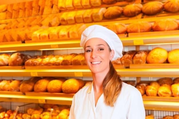Weiblicher bäcker, der brot in der bäckerei verkauft Premium Fotos