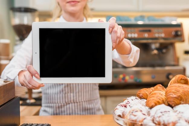 Weiblicher bäcker, der digitale tablette vor gebackenem hörnchen auf dem zähler zeigt Kostenlose Fotos